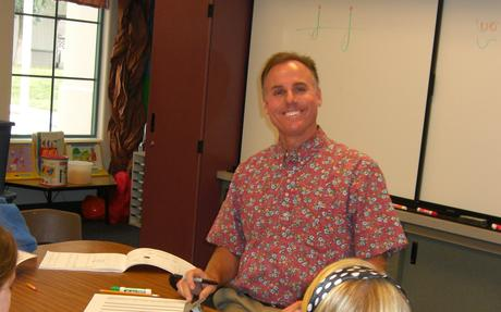 Mr. Coon smiling while working with a group of students.